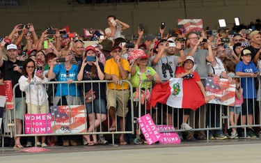 """People wait to hear U.S. President Donald Trump speak at his """"Make America Great Again Rally"""" at Orlando-Melbourne International Airport in Melbourne, Fla., Saturday, Feb. 18, 2017.  (AP Photo/Susan Walsh)"""