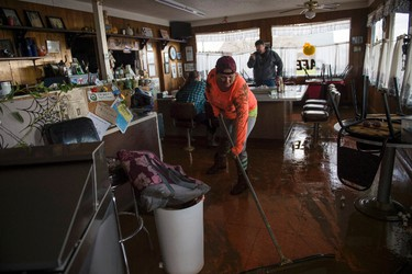 Tina Dry mops up water and mud that seeped into her family diner, Kim's County & Cafe, after area storms brought flood-level water to the Colusa County town of Maxwell, Calif. Saturday, Feb. 18, 2017. (Andrew Seng/The Sacramento Bee via AP)