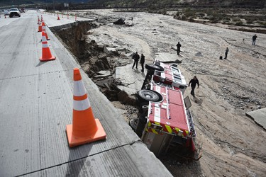 Officials look over the scene where a San Bernardino County Fire Department fire engine fell Friday from southbound Interstate 15 where part of the freeway collapsed due to heavy rain in the Cajon Pass, Calif., Saturday, Feb. 18, 2017. (David Pardo/The Daily Press via AP)