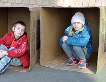 Joshua, 8, and sister Isabelle Lariviere, 12, sit in boxes symbolic of youth homelessness at the Push for Change Sleepout Challenge in St. Marys Saturday.