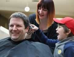 Gavin Cooper, 6, can't control his excitement shaving his father Mark, a Sarnia firefighter, at the Shave for the Brave event held at Lambton Mall Sunday. More than 20 Sarnia-Lambton first responders went under the clippers to raise $15,000 for pediatric cancer research. Pictured here with the Coopers is hairdresser Jessica Daborn, of Trendsetters Hair Studio. Barbara Simpson/Sarnia Observer/Postmedia Network
