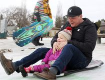 Jon MacDonald and daughter Edan, 2, take a toboggan ride down Thrill Hill during the Swanavon and Highland Park Neighbourhood Association's Winter Blast activities on  Saturday February 18, 2017 in Grande Prairie, Alta. Neighbourhood associations throughout the city held Winter Blast events over the long weekend. Kevin Hampson/Grande Prairie Daily Herald-Tribune/Postmedia Network