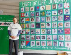 Wayne Burrow, owner of Suits Us in Hanover, stands beside a printed copy of a quilt honouring organ donors and recipients. The original quilt is on display at London Health Sciences Centre. Burrow is hoping to raise awareness about the importance of organ donation. (Dave Flaherty)
