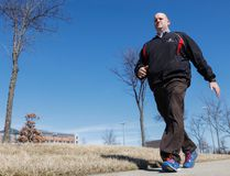 In this Monday, Feb. 29, 2016, photo, Brett Broviak, a manager of respiratory and sleep services at IU Health North Hospital, walks with his Fitbit fitness tracker on the hospital's campus in Carmel, Ind. (AP Photo/AJ Mast)