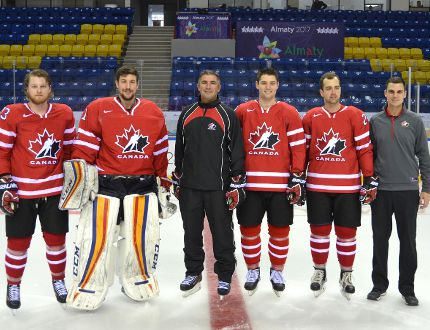 James Sawchuk (on the right) stands beside the Queen's University hockey players and coach that represented Canada at the Universiade Games. Sawchuk was an athletic therapist with the national team.