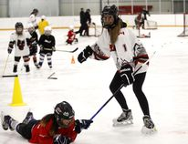 Smiles-Lots of smiles as Jaden Bearspaw is pulled by midget player Morgan Boot via a stick during Girl's Hockey Day.