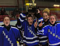 Members of the Simcoe Sabres girls hockey team – Veronica Samborski, Kassie Courrier, Emily Shuttleworth and Haven Swarts – celebrate their team's 5-1 win over Holy Trinity to claim the NSSAA title Wednesday at Talbot Gardens. Courrier and Swarts combined for four of the team's five goals on the afternoon. JACOB ROBINSON/SIMCOE REFORMER