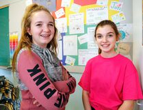 """Luke Hendry/Th Intelligencer Students Hannah Hoffman, left, and Olivia Millar stand in front of the """"respect wall"""" at Holy Rosary Catholic School Wednesday in Belleville. It's covered with students' descriptions of ways in which they will be more respectful - one of many activities surrounding Pink Shirt Day, a campaign against bullying."""