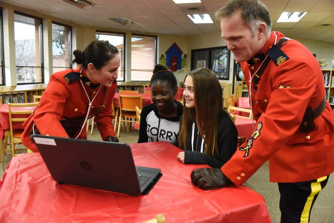 Grande Prairie RCMP Const. Gabrielle Spencer (left) and Cpl. Shawn Graham show Crystal Park School students Angilique Pottinger (center left) and Paris Robert the new Lead and Learn program on Thursday February 23, 2017 in Grande Prairie, Alta. Twenty students at the school will receive laptops from the detachment as part of the RCMP Foundation's TechConnect program, which connects deserving students with computers and mentorship by an RCMP officer. The officer teaches the students about internet safety and etiquette. Svjetlana Mlinarevic/Grande Prairie Daily Herald-Tribune/Postmedia Network
