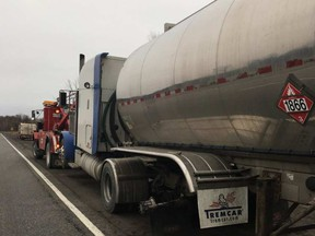 A tow truck hooks up a tanker trailer that lost a wheel Friday morning, striking five other vehicles. OPP photo