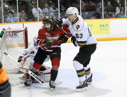 Owen Sound Attack winger Ethan Szypula (left) gets smacked in the head by the London Knights' Cliff Pu (right) during first period Ontario Hockey League action on Saturday. There was no penalty on the play.