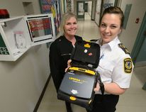 Miranda Bothwell, public education coordinator for Middlesex-London EMS, right, and Mary Ellen cornelius, principal of St Martins Catholic School, show Automatic External Defibrillator in the hall of the school. (MORRIS LAMONT, The London Free Press)