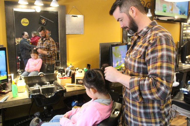 Kings and Little Ones owner Josh Casselman adjusts a shoe bun on his daughter, Kori-Anne, during the Daddy and Daughter Hair Survival fundraiser on Sunday . Greg Peerenboom/Cornwall Standard-Freeholder