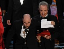 """Actor Warren Beatty (C) shows the card reading Best Film 'Moonlight"""" after mistakingly reading """"La La Land"""" initially at the 89th Oscars on February 26, 2017 in Hollywood, California. / AFP PHOTO / Mark RALSTONMARK RALSTON/AFP/Getty Images"""