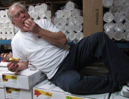 Gus Pantazis stretches out on cases of fruit fillings Saturday to enjoy a paczki made in the kitchen of his Global Donuts and Deli on London Road in Sarnia. The shop has been making the Polish pastries in the days leading up to Lent for the last three decades. (Paul Morden/Sarnia Observer)