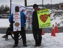 Isadore Pangowish and John Wemigwans holding signs at rally. Photo by Leslie Knibbs/For The Mid-North Monitor