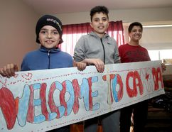 Ibraheim Al Jalam, right, cousin of sick Syrian boy Bilal Al Jalam, holds up a welcome to Canada sign with Syrian-Kingston friends Ouday Al Jalem, middle and Kousay Al Jalem on Monday. (Ian MacAlpine/The Whig-Standard)