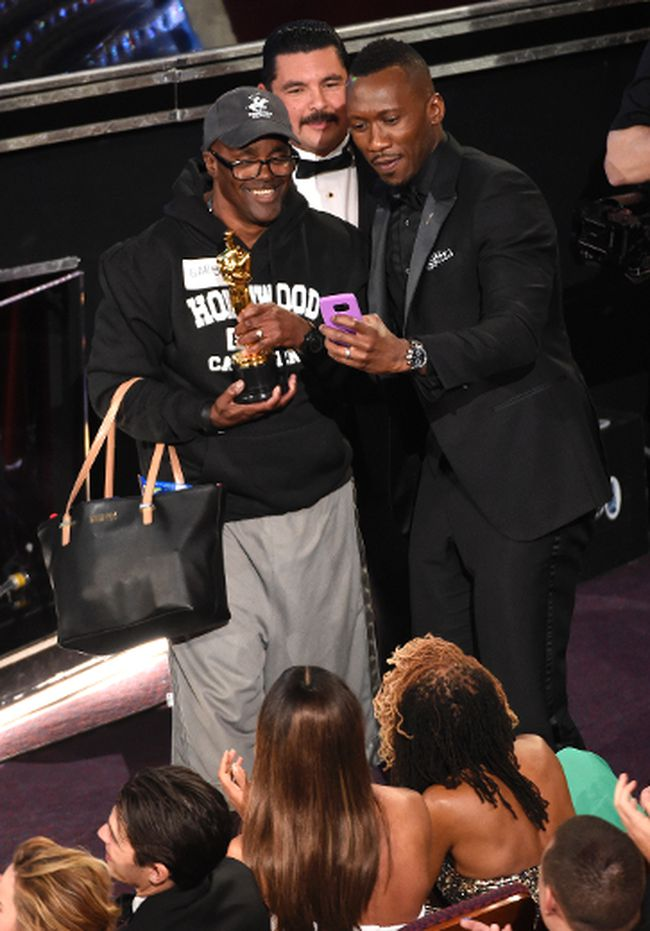 """Mahershala Ali, right, takes a selfie with a tourist named Gary while holding his award for best actor in a supporting role for """"Moonlight"""" at the Oscars on Sunday, Feb. 26, 2017, at the Dolby Theatre in Los Angeles. (Photo by Chris Pizzello/Invision/AP)"""