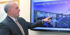 In this file photo, Canadore College president George Burton points to a feature on an artist's impression of the Village Living Wellness and Learning Centre.