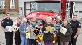 West Perth Fire Department Captain Mike Montgomery (left) and firefighter Cody Feltz accepted a generous donation of new teddy bears, books and toys from the Gould's WI recently. Making the presentation were Marion McKay, Marg French, Jean Morris, Renata Rose, Hollie Archer and Marlene Archer. ANDY BADER/MITCHELL ADVOCATE