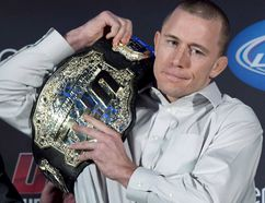 Welterweight UFC champion Georges St. Pierre put his belt on his shoulder during a news conference in Montreal on Jan. 23, 2013. (THE CANADIAN PRESS/Paul Chiasson)