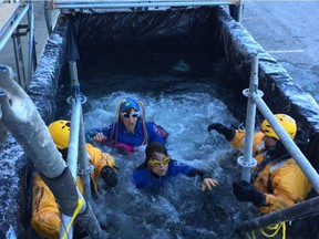 Looks of shock are frozen on volunteers' faces as they emerge from the water. ELISE SCHULZKE/POSTMEDIA