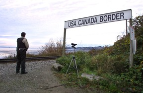 A Canadian Customs and Fisheries officer watches over the U.S.-Canada border between Blaine, Washington and White Rock, British Columbia November 8, 2001 in White Rock, BC. (Photo by Jeff Vinnick/Getty Images)