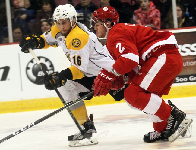 Sarnia Sting defenceman Jordan Ernst (left) and Soo Greyhounds defenceman Noah Carroll race for the puck during first-period play Wednesday in Sault Ste. Marie. Jeffrey Ougler/Sault Star/Postmedia Network