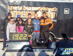 Dave Marshall, dressed in blue, stands with family and friends after getting his snowmobile up 192.2 mph. (Contributed photo)