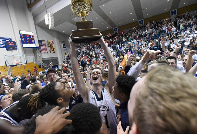 In this Tuesday, March 7, 2017, file photo, Mount St. Mary's forward Will Miller, center, celebrates with teammates after beating St. Francis (Pa.) 71-61 in the NCAA college basketball Northeast Conference Tournament championship, in Emmitsburg, Md. With the win, Mount St. Mary's earned an automatic berth to the NCAA Tournament. The 67-game March Madness basketball tournament begins Tuesday, March 14, with many games taking place during the work day. All of the games will be available online. For many of the early-round games, though, you'll need a password through your cable or satellite TV subscription. (AP Photo/Steve Ruark, File)