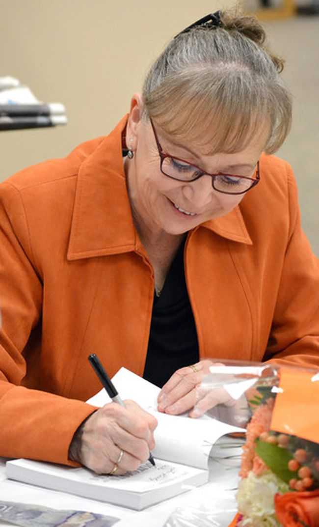 Jacqueline Guest signs one of her books at the Cochrane Public Library after reading from The Comic Book War, one of her most recent young adult novels written to put World War Two into a local context.