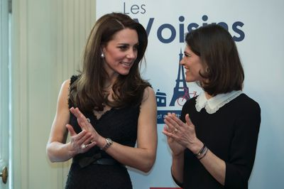 Kate, Duchess of Cambridge, and the wife of Britain's ambassador to France Lord Ed Llewellyn, Anna, listen to Prince William during a reception at the British embassy in Paris, Friday, March 17, 2017. The duchess is wearing a black Alexander McQueen dress. (Ian Langsdon/pool Photo via AP)