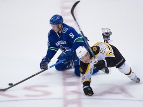 Boston Bruins right wing David Pastrnak (88), of the Czech Republic, falls over Vancouver Canucks defenceman Troy Stecher (51) during the third period of an NHL hockey game in Vancouver, B.C., on Monday March 13, 2017.