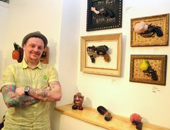 The Meet Your Maker Gallery and Gift Shop in Stratford held an open house for its Show & Tell art exhibition Saturday evening. Pictured, gallery owner and artist, Leigh Cooney, shows off some of non-traditional art on display until the end of the month, including his piece, Mr. Tayto Head, and a collection of gun-themed work by Vivian Hutcheson. Galen Simmons/The Beacon Herald/Postmedia Network
