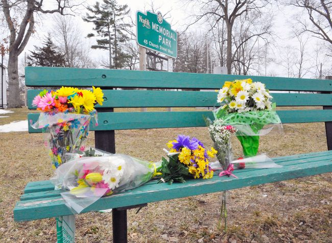Bouquets of flowers have been left on a park bench on King Street in Delhi near where Sally Ann Dollard, 72, was killed by a hit-and-run driver Friday. JACOB ROBINSON / SIMCOE REFORMER