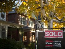 A real estate sold sign hangs in front of a west-end Toronto property. THE CANADIAN PRESS
