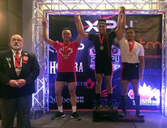 Brockville's Christopher Dang (middle) stands at the top of the podium after finishing first in the 74 kg division at the national powerlifting championships in Saguenay, Que. He will now be representing Canada at the world championships in Belarus in June. (Contributed photo)
