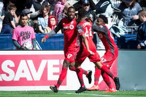 From left, Toronto FC's Jozy Altidore, Raheem Edwards and Tosaint Ricketts celebrate Altidore's goal against the Whitecaps last weekend. Edwards was awarded his first MLS assist on the play.(The Canadian Press)
