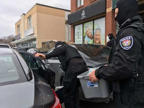 Police carry out cannabis products from Magna Terra. JACQUIE MILLER / POSTMEDIA