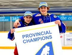 McMurrayites Jesse Burchart, left, and Sebastian Cossa, right, hold up the banner after they defeated Lethbridge 2-1 in game five of the AMBHL Championship Wednesday. The pair will now play in the Western Canadian Bantam championship at the end of the month. Photo supplied/Sandie Cossa
