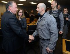 Outgoing police services board member Paul Paolatto shakes hands with officers from the emergency response unit following his final board meeting Thursday at London police headquarters. (MORRIS LAMONT, The London Free Press)