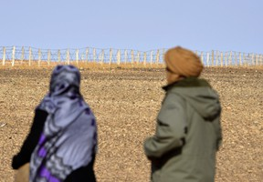 This photo taken on February 3, 2017 shows Zghala, a woman from Western Sahara, looking at the fence in the Al-Mahbes area as she accompanies her 14-year-old son to show him the wall separating the Polisario controlled Western Sahara from Morocco on.  Built to keep out migrants, traffickers, or an enemy group, border walls have emerged as a one-size-fits-all response to the vulnerability felt by many societies in today's globalized world, says an expert on the phenomenon. STRINGER/Getty Images
