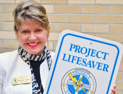 Michele Hough, the local volunteer co-ordinator of Project Lifesaver, with an example of the new signage that will soon be posted at high-traffic areas around Norfolk County. MONTE SONNENBERG / SIMCOE REFORMER