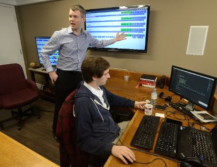 Ben Whitney, of Armo Tool, left explains the monitoring displays during a tour of FreePoint Technologies. At right is FreePoint employee Nicholas Marcon. (MORRIS LAMONT, The London Free Press)