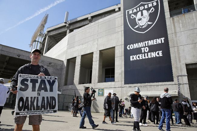 John P. Kelleher holds up a sign outside the Oakland Coliseum before the start of a rally to keep the Oakland Raiders from moving Saturday, March 25, 2017, in Oakland, Calif. (AP Photo/Eric Risberg)