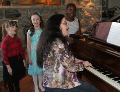 Alison Kirkpatrick, a music instructor who teaches vocal, provides piano accompaniment as Ava Dupont, from left, Kaitlyn Skinner and Natalie Graham rehearse as a trio for their upcoming performance at the Porcupine Music Festival. The festival kicks off on Wednesday.