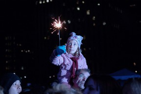 A child holds a sparkler during the Earth Hour 2009 event in Nathan Phillips Square in Toronto. (Postmedia Network files)