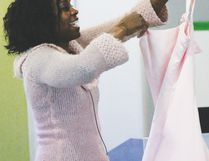 I Am Empowered Women's Conference Keynote Speaker Alison Springer holds up a pale pink bridesmaid dress she was forced to wear once for a friend's wedding. She encouraged participants at the conference not to be afraid to wear pink and not to apologize for being a girl.
