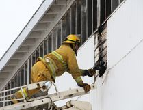 Fire crews used the ladder truck to inspect the outside wall of the Melfort Grandstand after it caught fire on Sunday, March 26.