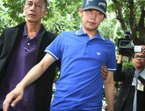 """In this Sept. 3, 2012, photo, Vorayuth """"Boss"""" Yoovidhya, centre, whose grandfather co-founded energy drink company Red Bull, is escorted by police in Bangkok, Thailand. (Thai Daily News via AP)"""